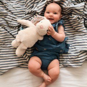 niemowlak leży i śmieje się oraz trzyma szumiącego króliczka Whisbear