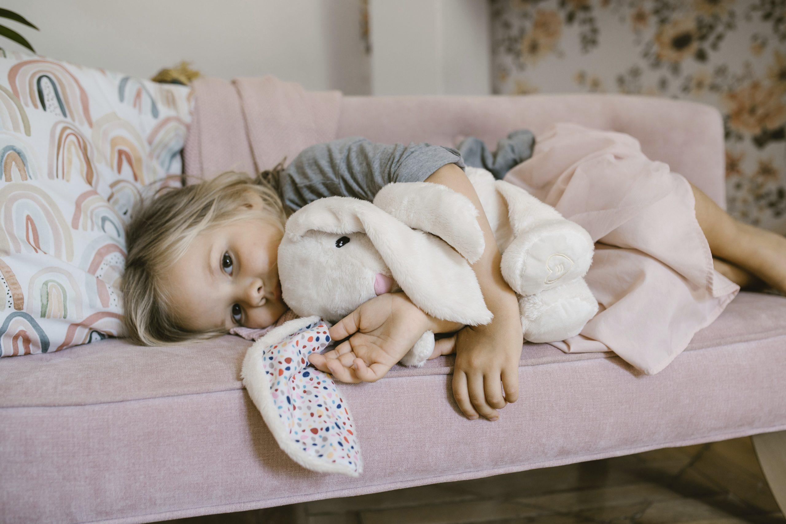 dziewczynka leżąca na kanapie z szumiącym Króliczkiem Whisbear