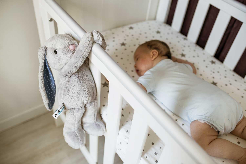 niemowlak śpi w kojcu z przywieszonym szumiącym króliczkiem na poręczy