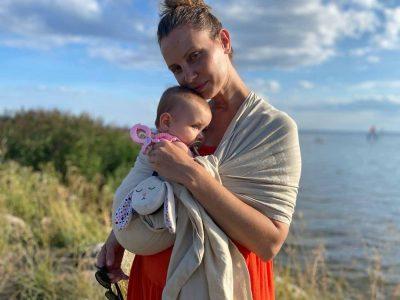 mama przytula niemowlaka owiniętego kocem