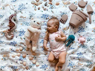 niemowlak leżący na kołdrze z misiem szumiącym Whisbear