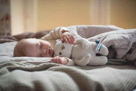 śpiący niemowlak trzymający szumiącego misia