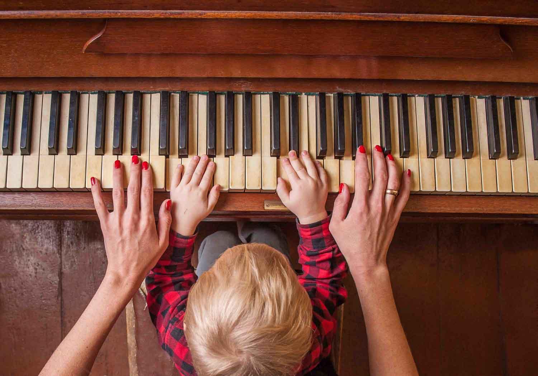 mama z niemowlakiem grają na pianinie na cztery ręce