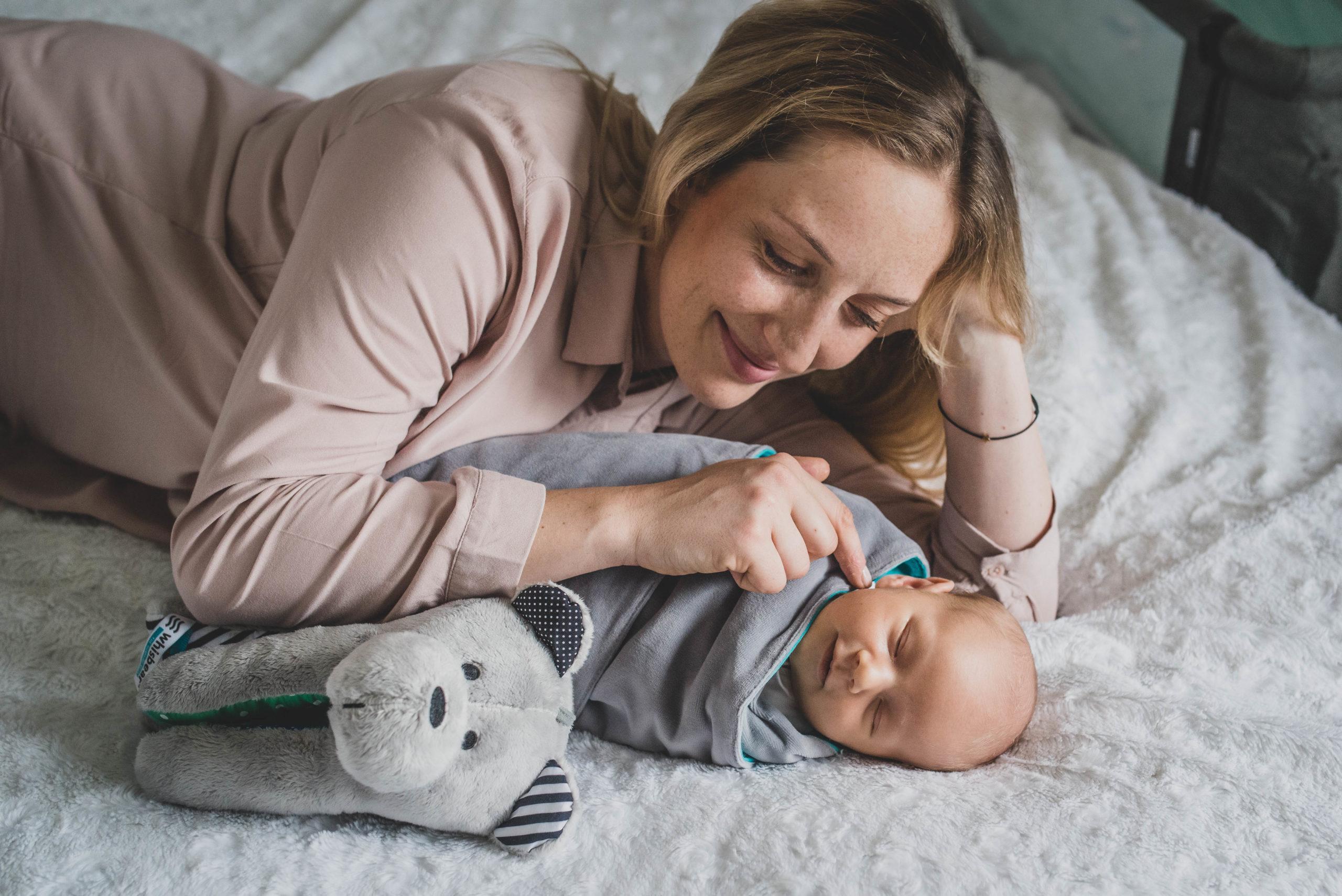 mama leżąca z niemowlakiem owiniętym w szary kocyk, obok szumiący miś sensoryczny Whisbear