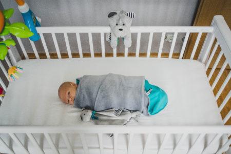 niemowlak leżący w łóżeczku, w szarym kocyku od Whisbear, na poręczy wisi szumiący miś sensoryczny Whisbear