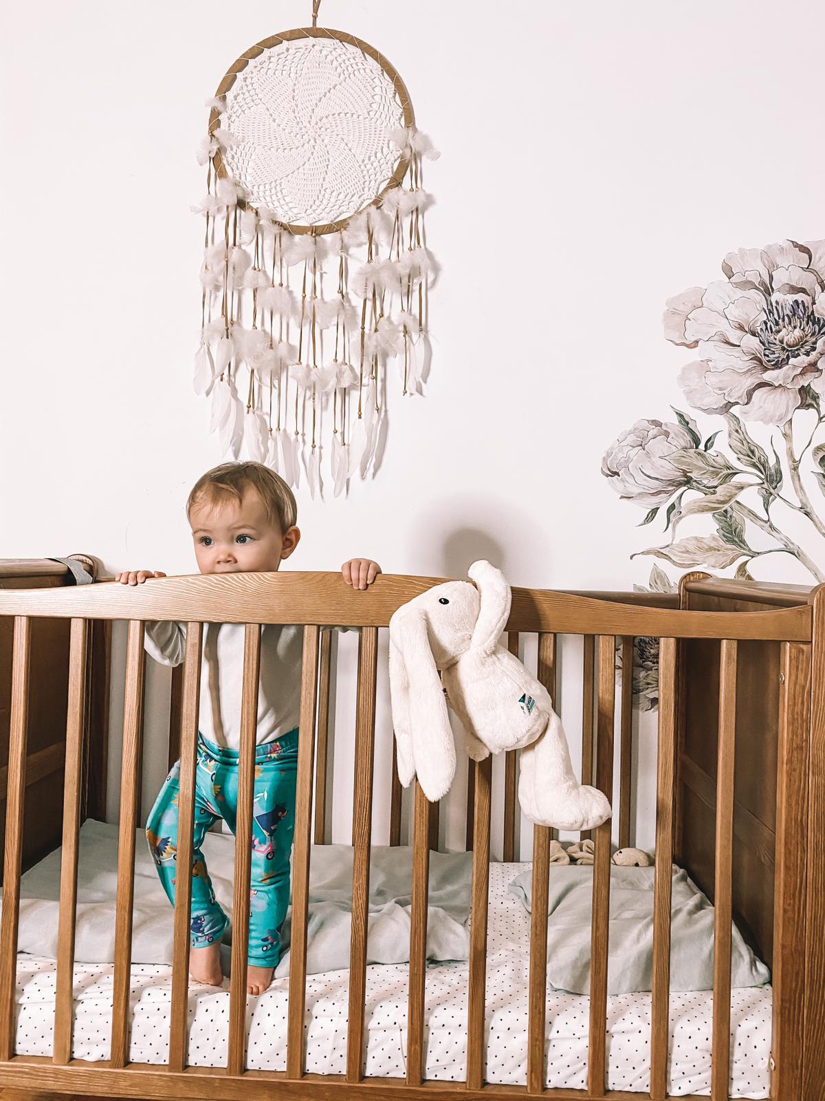 około dwuletnie dziecko stojące w łóżeczku i podgryzające balustradkę, obok wiszący dream catcher oraz szumiący króliczek Whisbear