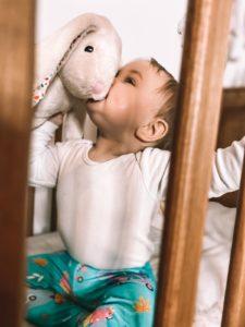 dziecko trzymające i lekko gryzące szumiącego króliczka Whisbear