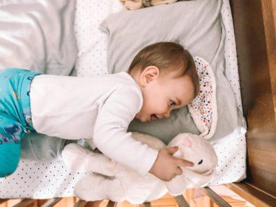 dziecko leżące w łóżeczku i trzymające szumiącego króliczka Whisbear