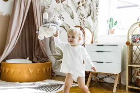 dwuletnie dziecko w białej koszulce trzyma w jednej rączce szumiącego misia Whisbear