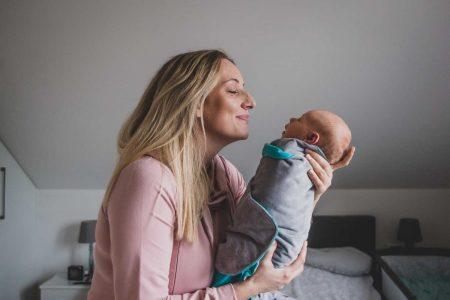 mama trzyma na rękach niemowlaka i uśmiecha się do niego