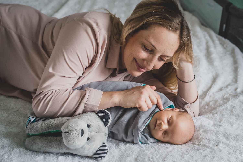 uśmiechnięta mama leży obok noworodka i misia sensorycznego Whisbear