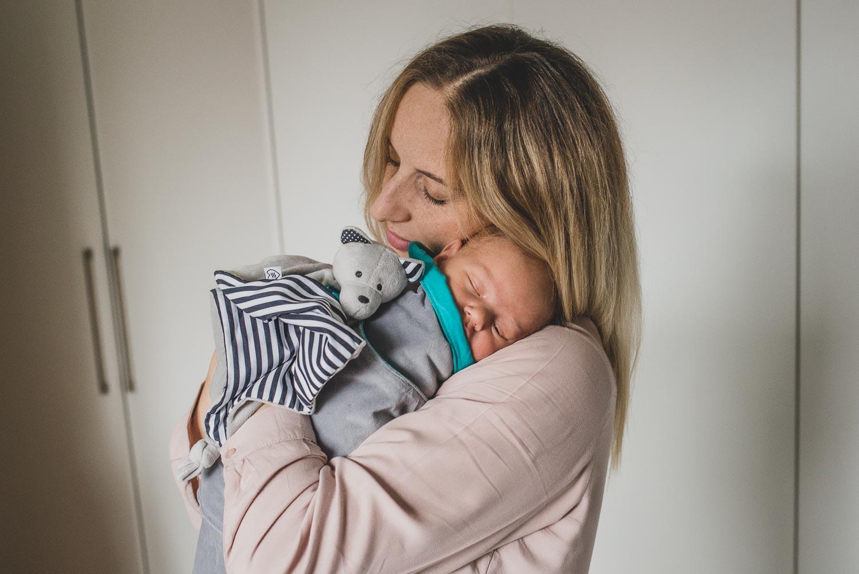 matka tuląca śpiącego niemowlaka