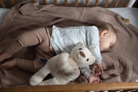 dziecko śpiące w łóżeczku z szumiącym misiem Whisbear obok