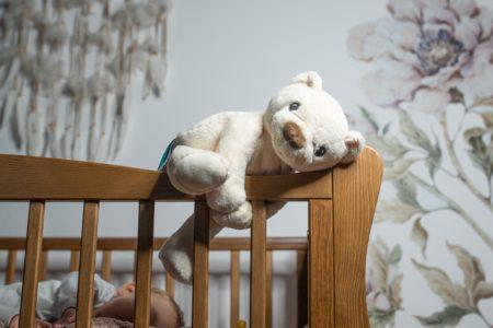 szumiący miś Whisbear oparty na poręczy łóżeczka