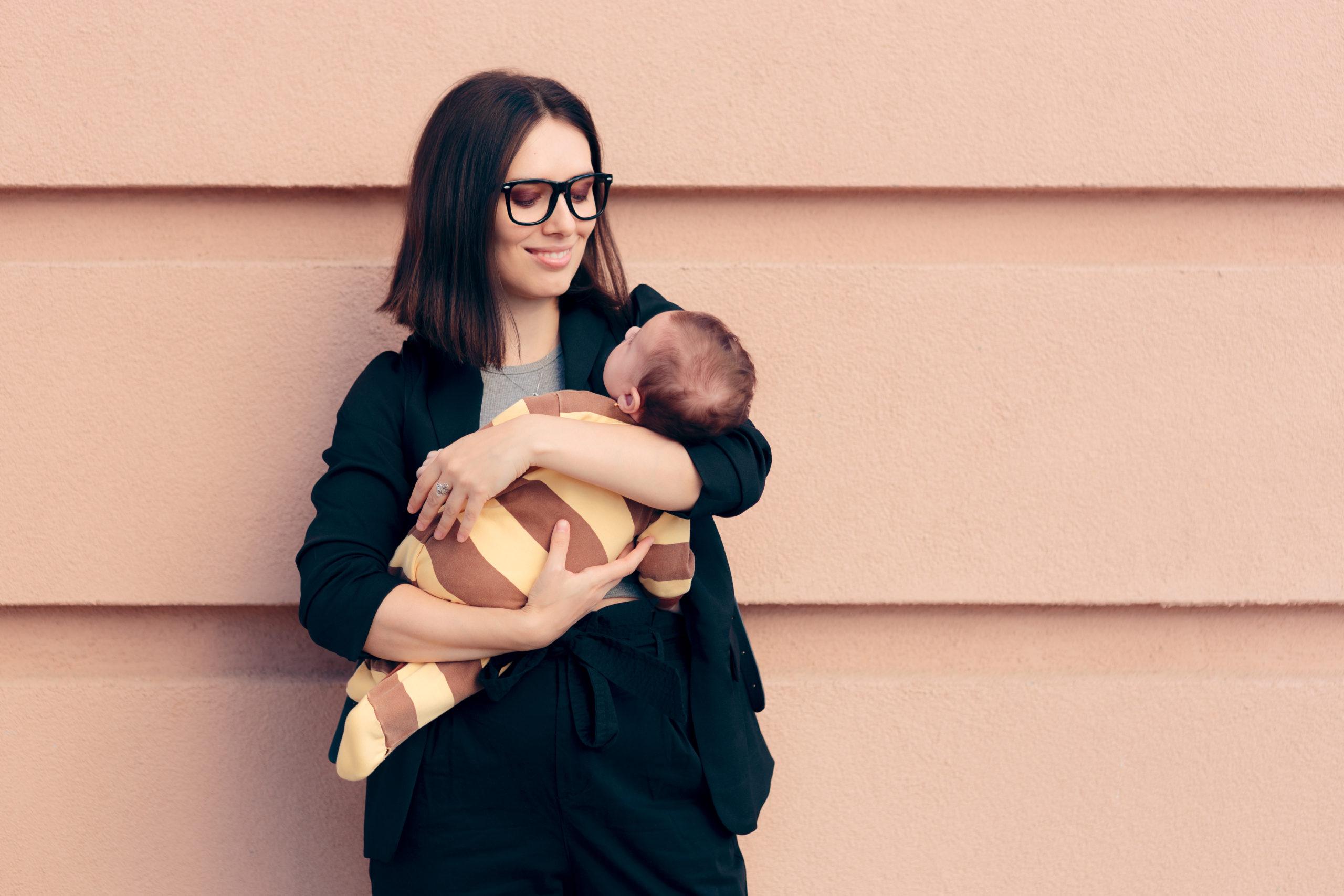 mama trzymająca zawiniętego w kocyk niemowlaka