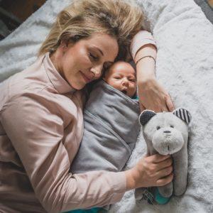 mama leżąca uśmiechnięta z zamkniętymi oczami przy śpiącym niemowlaku, w ręku trzyma szumiącego misia sensorycznego Whisbear